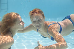 Young woman swimming  Under water. Young women swimming  Under water with joy Stock Photo