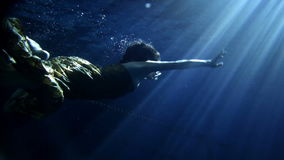 Young woman swimming under water in beautiful dress. Underwater activity and woman swimming under water in clothes stock video footage