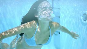 Young woman swimming underwater with closed eyes. Young woman swimming underwater in a swimming pool with reflections of the sunlight with closed eyes and arms stock video