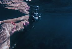 Sun glare on body of female freediver. Young woman swimming underwater surface. Sun glare on body of female freediver Stock Images