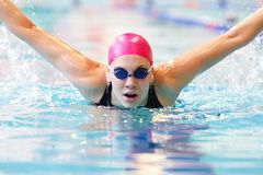 Young woman swims the butterfly Royalty Free Stock Photo