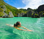 Young woman swims in the crystal clear water near of islands. Happy young woman swims in the crystal clear water near of amazing forms islands Stock Photo