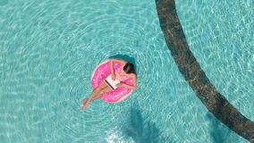 Young woman swims in the sea in a swimming circle. Girl resting in the pool on an inflatable circle with a computer, top. View royalty free stock photo