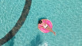 Young woman swims in the sea in a swimming circle. Girl resting in the pool on an inflatable circle with a computer, top stock images