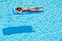 Young woman in swimsuit bakes lying on inflatable mattress Royalty Free Stock Image