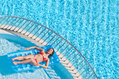 Young woman in swimsuit bakes lying on inflatable mattress Royalty Free Stock Photo