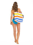 Woman in swimsuit with beach bag going straight. Young woman in swimsuit with beach bag going straight . rear view Royalty Free Stock Photos