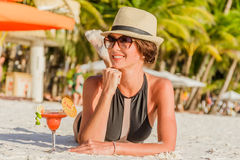 Young woman in swimsuit with cocktail on the beach in trop Royalty Free Stock Photo