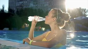 Young woman in a swimsuit drinks cool water from a plastic bottle in the pool stock footage