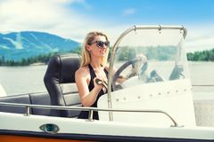 Young woman in a swimsuit driving a motor boat. royalty free stock image