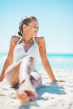 Young woman in swimsuit enjoying sitting on beach Stock Photos