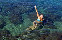 A young woman in swimsuit floats in seawater. Large space for writing royalty free stock images