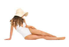 Young woman in swimsuit and hat laying on floor Royalty Free Stock Photo