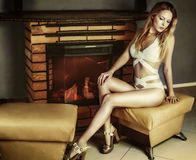 Young woman in swimsuit on the heels sitting near fireplace Stock Photography