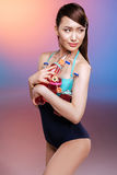 Young woman in swimsuit holding bottles with refreshing summer drinks and looking away Royalty Free Stock Photography