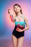 Young woman in swimsuit holding glass bottles with refreshing beverages and smiling Stock Image
