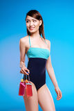 Young woman in swimsuit holding glass bottles with refreshing beverages and smiling Royalty Free Stock Photography