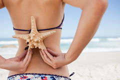 Young woman in swimsuit holding a starfish on her back Stock Photos
