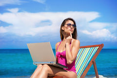 A young woman in a swimsuit and with a laptop on the beach. A young woman relaxing with a laptop on a beautiful beach Stock Photos