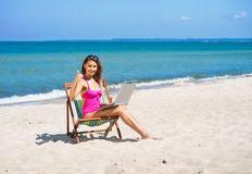 A young woman in a swimsuit and with a laptop on the beach. A young woman relaxing with a laptop on a beautiful beach. The image is taken during the summer Royalty Free Stock Photography