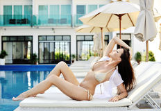Young woman in swimsuit laying on chaise-longue Royalty Free Stock Image