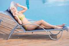 Young woman in swimsuit laying on chaise-longue poolside Royalty Free Stock Photo