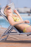 Young woman in swimsuit laying on chaise-longue poolside Stock Photography