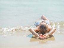 Young woman in swimsuit laying on sea shore. rear view Royalty Free Stock Photography