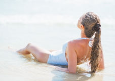 Young woman in swimsuit laying at seaside. rear view Stock Photo