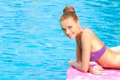 Young woman in swimsuit lying close to pool Stock Images