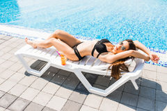 Young woman in swimsuit lying with cocktail on chaise longue. Summer time Royalty Free Stock Photography