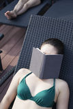 Young woman in a swimsuit lying down and relaxing with a book over her face Stock Photo