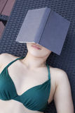 Young woman in a swimsuit lying down and relaxing with a book over her face Royalty Free Stock Image