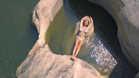 Young woman in swimsuit lying on large stone in river water drone view. Beautiful woman relaxing and sunbathing on. Big rock in river aerial view stock video