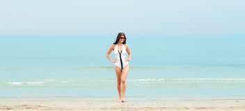 Young woman in swimsuit posing on beach Stock Photo