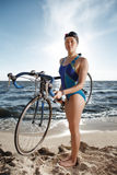 Young woman in swimsuit posing with road bike Stock Image