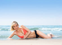 A young woman in a swimsuit relaxing on the beach Royalty Free Stock Photo