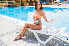 Young woman in swimsuit relaxing with cocktail on chaise-lounge. Young woman in swimsuit relaxing with cocktail on chaise-longue Royalty Free Stock Photos