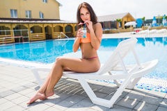 Young woman in swimsuit relaxing with cocktail on chaise-lounge. Young woman in swimsuit relaxing with cocktail on chaise-longue Royalty Free Stock Photo