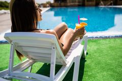 Young woman in swimsuit relaxing with cocktail on chaise-longue near pool in sunny day royalty free stock image