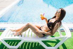 Young woman in swimsuit relaxing with cocktail on chaise longue. Summer time. Young woman in swimsuit relaxing with cocktail on chaise longue royalty free stock photo