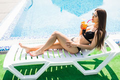 Young woman in swimsuit relaxing with cocktail on chaise longue. Summer time. Young woman in swimsuit relaxing with cocktail on chaise longue royalty free stock image