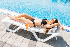 Young woman in swimsuit relaxing with cocktail on chaise longue . Summer time. Young woman in swimsuit relaxing with cocktail on chaise longue stock photography