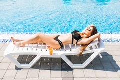 Young woman in swimsuit relaxing with cocktail on chaise longue. Summer time stock photos