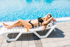 Young woman in swimsuit relaxing with cocktail on chaise longue. Summer time. Young woman in swimsuit relaxing with cocktail on chaise longue stock photo