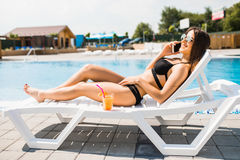 Young woman in swimsuit relaxing with cocktail on chaise longue and talk on phone . Summer time stock images