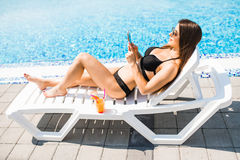 Young woman in swimsuit relaxing with cocktail on chaise longue and use her phone for texting. Summer time. Young woman in swimsuit relaxing with cocktail on stock images