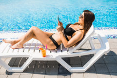 Young woman in swimsuit relaxing with cocktail on chaise longue and use her phone for texting. Summer time stock image