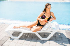 Young woman in swimsuit relaxing with cocktail near pool. Summer time Stock Photo