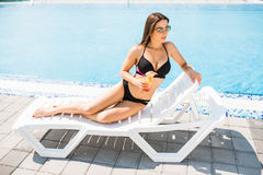 Young woman in swimsuit relaxing with cocktail near pool. Summer time Stock Images